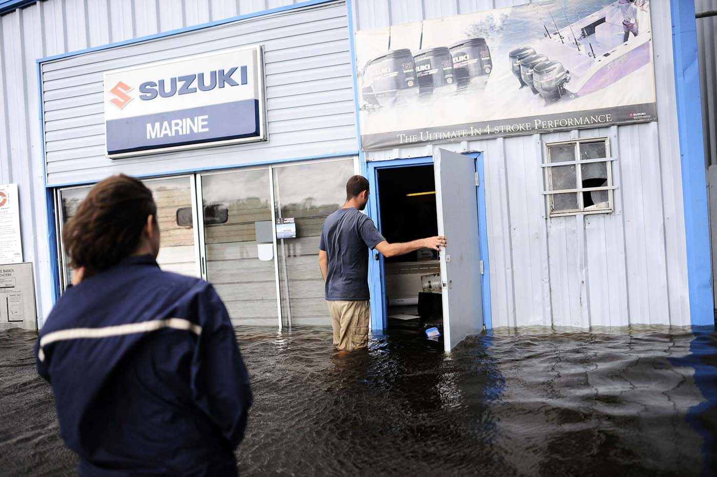 Eric Mylin and his girlfriend Misty Burk walk through his flooded business, the Magic Manatee Marina, as they inspect the damage caused by water associated with Tropical Storm Debby in Homosassa, Florida, June 26, 2012. (Brian Blanco/Reuters)