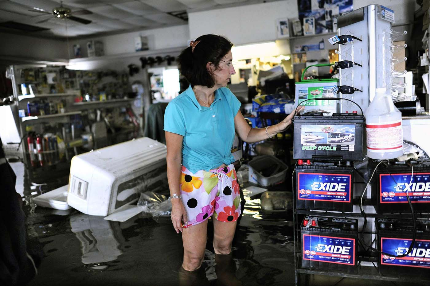 Doreen Mylin, owner of the Magic Manatee Marina, inspects the damage as the water associated with Tropical Storm Debby rises and floods her business in Homosassa, Florida, June 26, 2012. (Brian Blanco/Reuters)