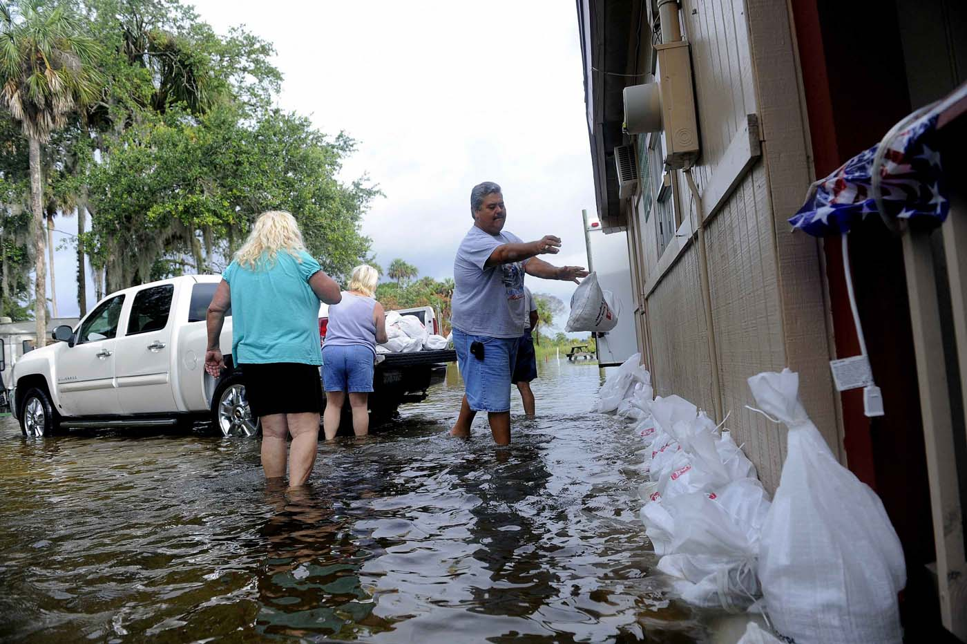 Mike Shoemaker (R), manager of the Nature's Resort RV Park, joins residents as they unload sandbags together to protect the park's bar and hold back rising floodwaters associated with Tropical Storm Debby in Crystal River, Florida, June 26, 2012. (Brian Blanco/Reuters)