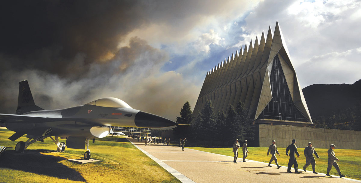 JUNE 27: Smoke from the Waldo Canyon Fire rises near the USAF Academy's Cadet Chapel as cadets head for a briefing on evacuation procedures, in Colorado Springs, Colorado, in this U.S. Air Force handout photo dated June 27, 2012. The Academy evacuated more than 600 families and 110 dormitory residents from the base on June 27. Photo taken June 27, 2012. (U.S. Air Force/Carol Lawrence/Handout/Reuters)