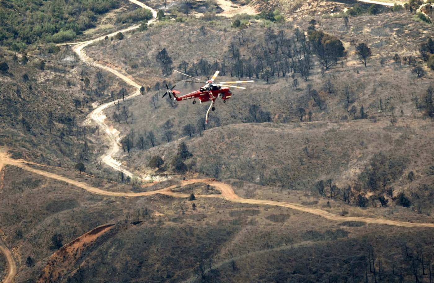 JUNE 28: A helicopter flies over the aftermath of the Waldo Canyon Fire in Colorado Springs, Colorado June 28, 2012. Cooler temperatures and lighter winds helped firefighters on Thursday in the battle against the fire, which has destroyed hundreds of homes and forced more than 35,000 people to flee. (Rick Wilking/Reuters)
