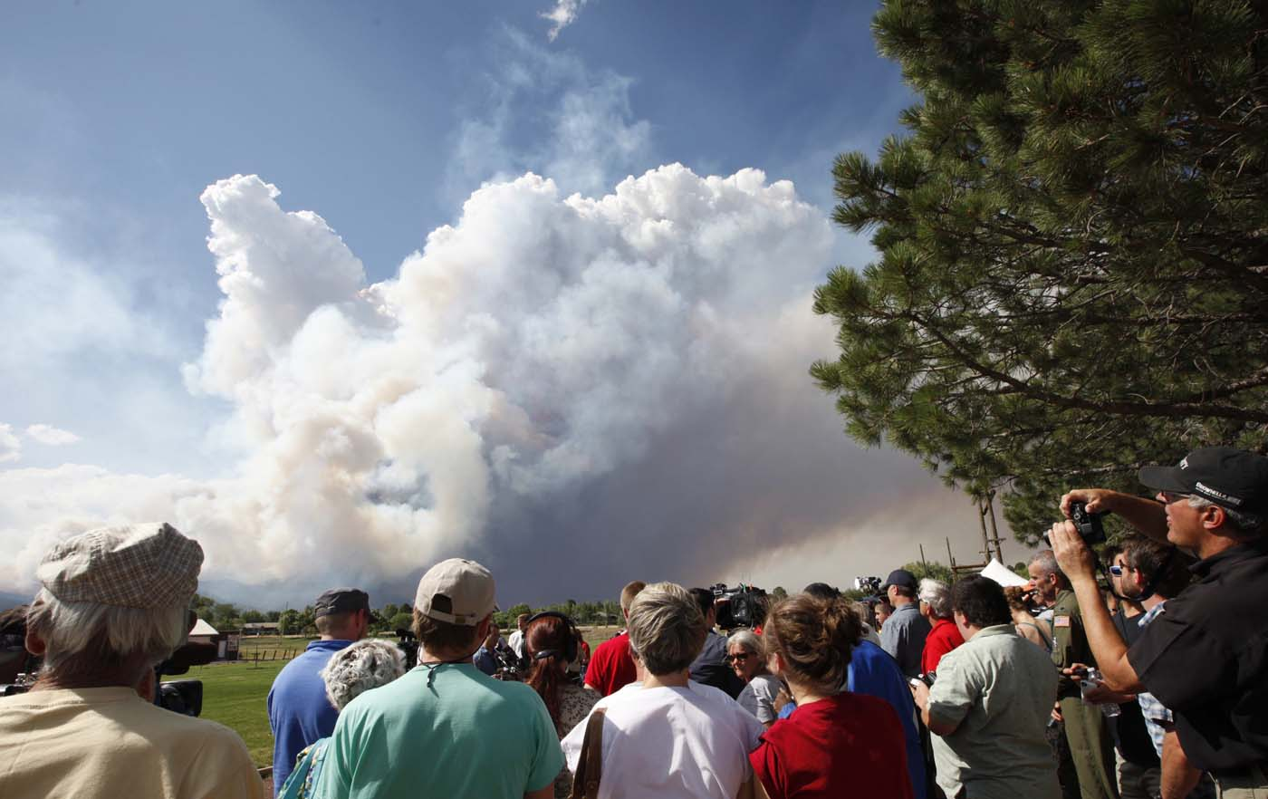 JUNE 26: Evacuated residents and others listen to a briefing as smoke rises from the Waldo Canyon fire west of Colorado Springs, Colorado June 26, 2012. (Rick Wilking/Reuters)