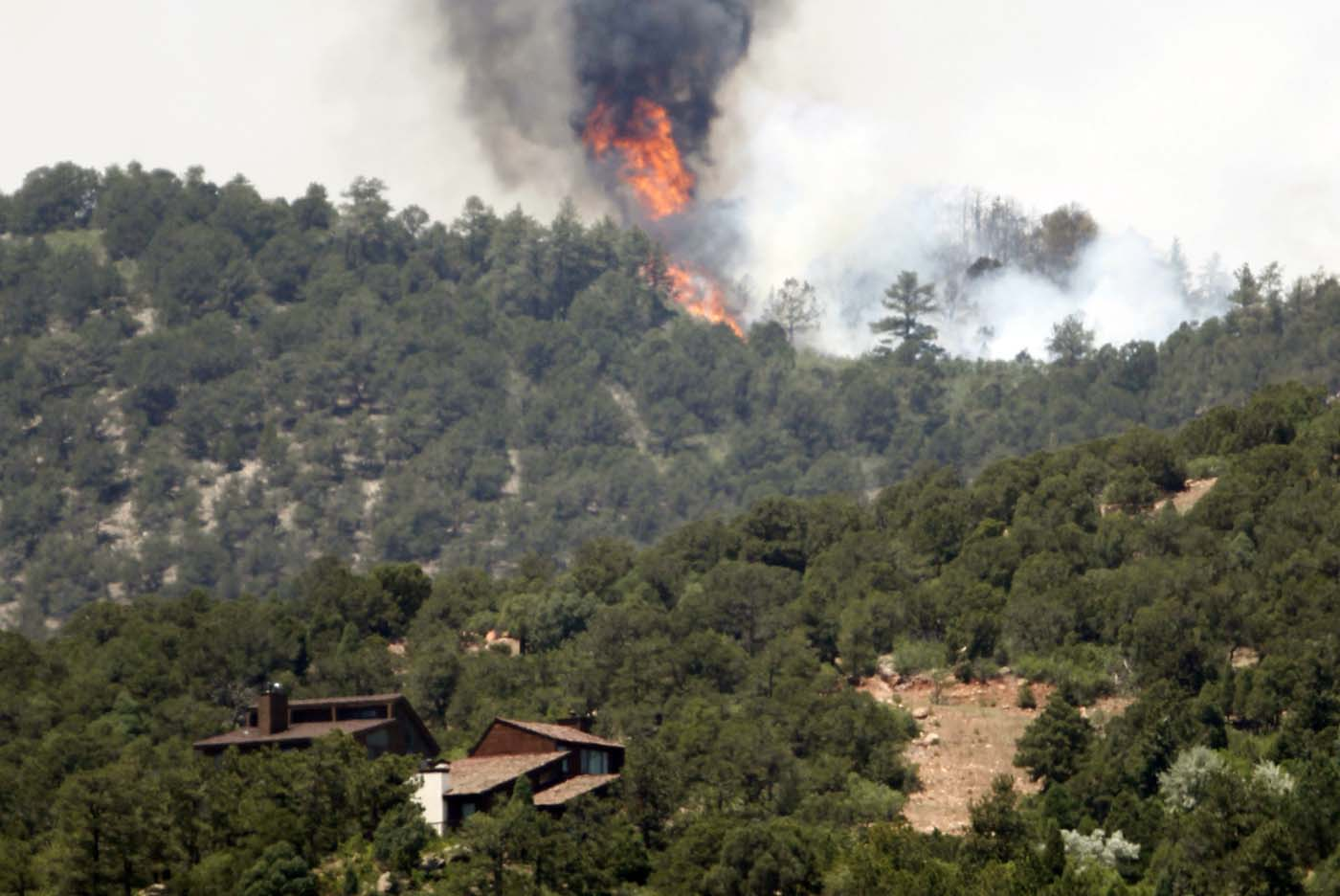 "JUNE 25: Fire continues to burn near homes in the Waldo Canyon fire west of Colorado Springs, Colorado June 25, 2012. A fast-growing wildfire in Colorado forced 11,000 people from their homes at least briefly and threatened popular summer camping grounds beneath Pikes Peak, whose vistas helped inspire the patriotic tune ""America the Beautiful."" (Rick Wilking/Reuters)"