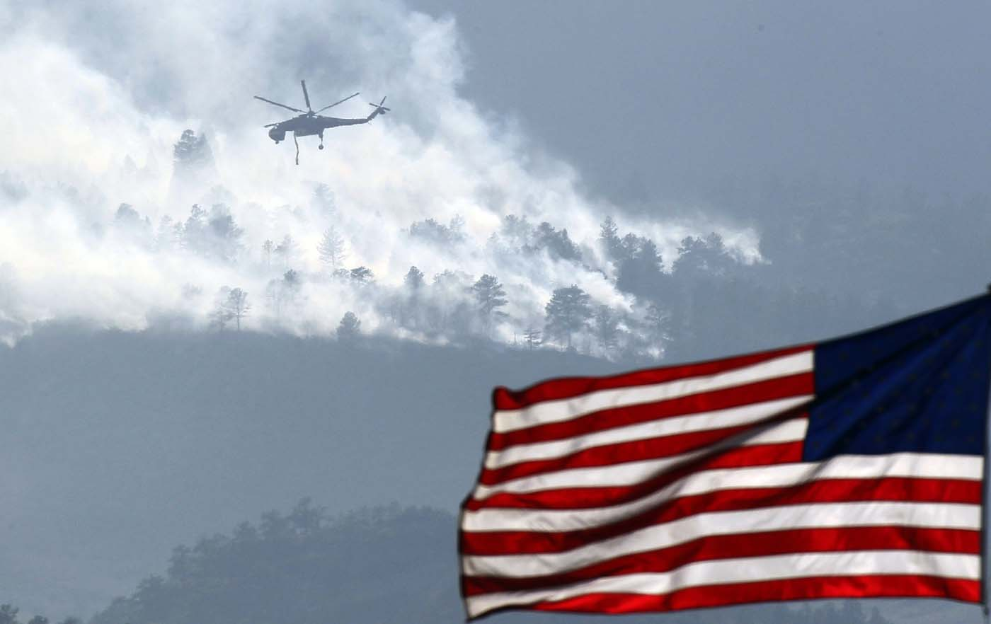 JUNE 27: A helicopter makes a pass before dropping water on the Waldo Canyon fire burning behind the U.S. Air Force Academy, west of Colorado Springs, Colorado June 27, 2012. (Rick Wilking/Reuters)