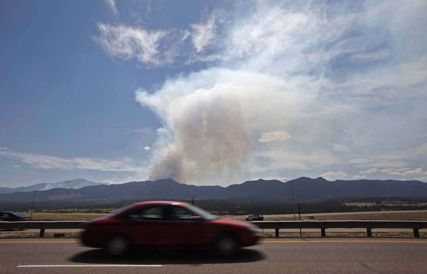JUNE 25: A car speeds down the highway past the Waldo Canyon fire sending up a smoke plume, which could be seen for miles, outside Colorado Springs, Colorado June 25, 2012. The out-of-control wildfire near some of Colorado's most visited tourist sites expanded overnight and kept some 6,000 people from their homes on Monday, as forecasts said winds could push the flames toward the U.S. Air Force Academy. (Rick Wilking/Reuters)
