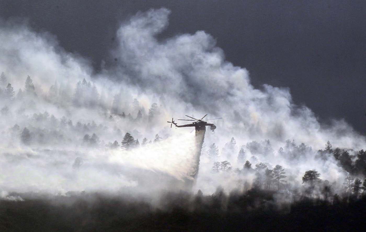 JUNE 27: A helicopter drops water on the Waldo Canyon fire burning behind the U.S. Air Force Academy, west of Colorado Springs, Colorado June 27, 2012. (Rick Wilking/Reuters)
