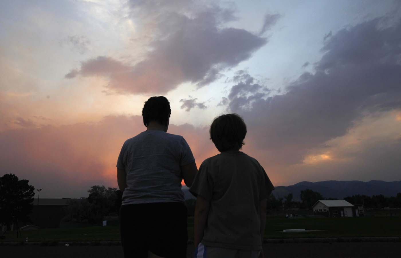 JUNE 24: People watch a giant smoke plume rising from the Waldo Canyon Fire during sunset, west of Colorado Springs June 24, 2012. The fast-growing wildfire that blew up overnight in Colorado has forced 11,000 people from their homes and was threatening popular summer camping grounds beneath Pikes Peak, billed as the most visited mountain in North America. (Rick Wilking/Reuters)