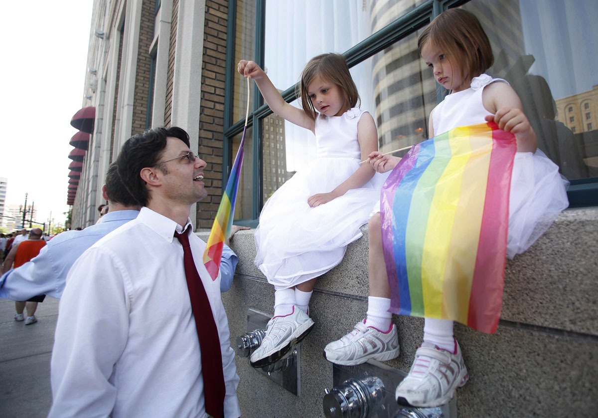 Salt Lake City: Practicing Mormon Chad Smith and his daughters Kathryn (C), 6, and Olivia, 4, attend a gay pride parade June 3, 2012. Over 300 active Mormons and more than 5,000 members of the Lesbian, Gay, Bisexual and Transgender (LGBT) community with their supporters marched in the parade as part of the Utah Pride Festival. (Jim Urquhart/Reuters)