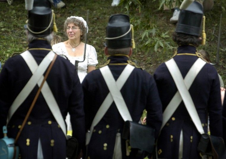September 3, 2006: As part of the Defenders' Day celebration, re-enactors will stage a re-enactment of the 1814 Battle of North Point where American troops slowed the advance of about 5000 British troops, which three weeks before had burned Washington. Jean Chriest (cq), of Dundalk, who is dressed in period clothing of a lady in the 1800s, watches the re-enactors, foreground, assemble for the flag ceremony. Chriest's husband is an re-enactor with Aisquith's Sharp Shooters 1812 Rifle Company. (Kenneth K. Lam/Baltimore Sun)