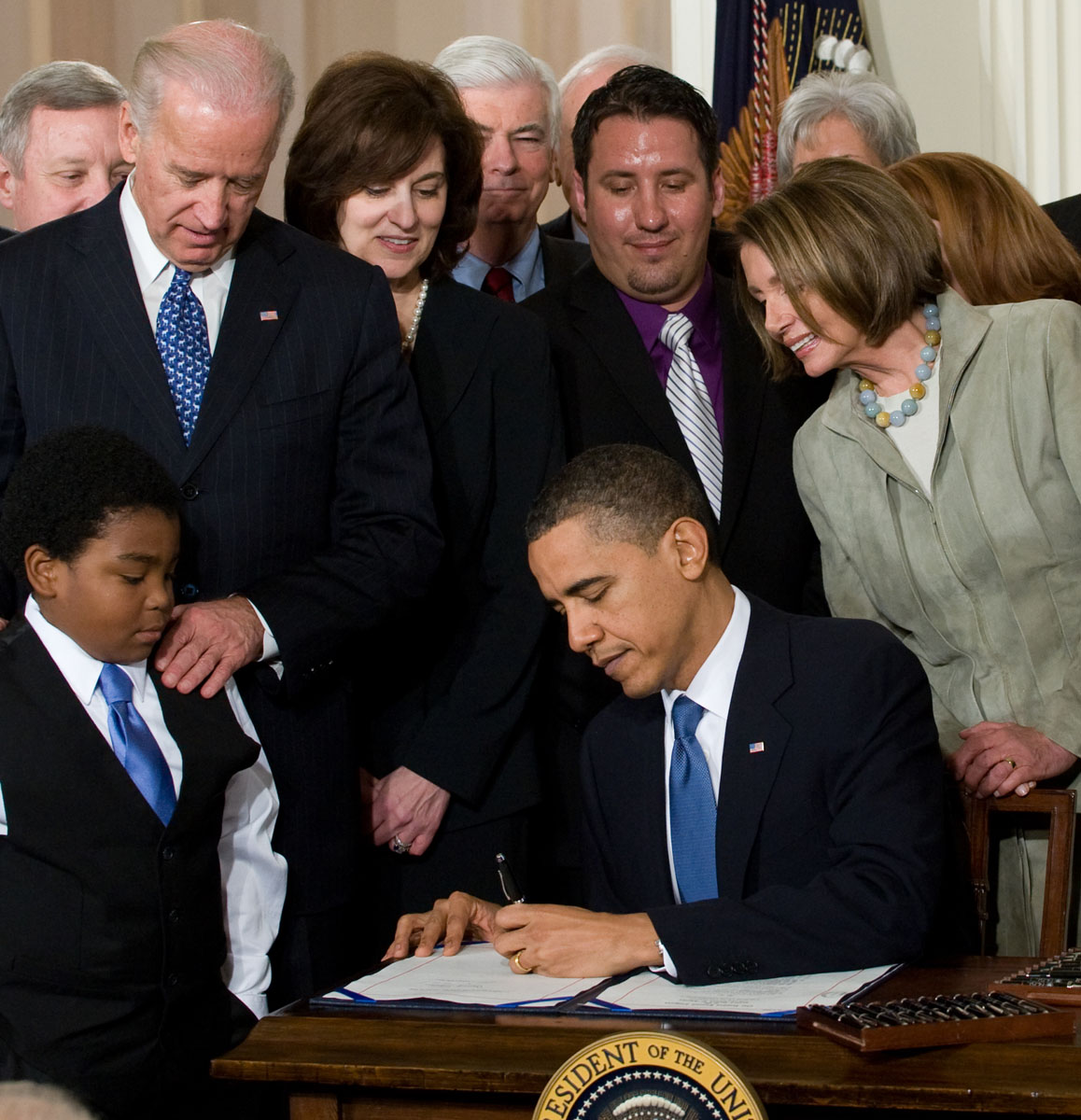 March 23, 2010: US President Barack Obama, surrounded by lawmakers and guests, signs the healthcare insurance reform legislation during a ceremony in the East Room of the White House in Washington on March 23, 2010. Obama signed into law his historic health care reform, enacting the most sweeping social legislation in decades which will ensure coverage for almost all Americans. (Saul Loeb/AFP/Getty Images)
