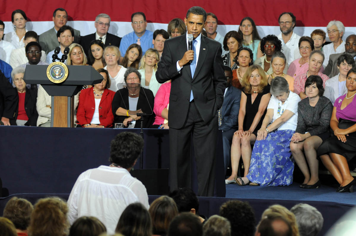 August 11, 2009: U.S. President Barack Obama listens to a question at a town hall meeting August 11, 2009 in Portsmouth, New Hampshire. President Obama spoke about the need for health insurance reform to a crowd of eighteen hundred. (Darren McCollester/Getty Images)
