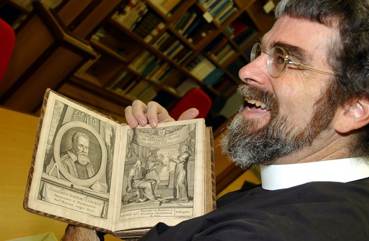 "Galileo Galilei, ""Father of modern science"" – Jesuit Brother and astronomer Guy Consolmagno, 50, opens a book by Italian 17th century astronomer Galileo Galilei (pictured at left) at the Vatican Observatory library on the outskirts of Rome on August 13, 2003. (AP Photo/Plinio Lepri)"