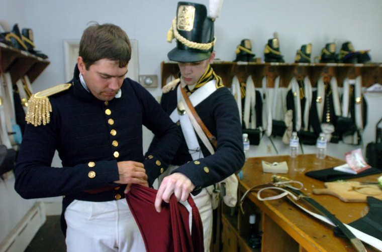 August 26, 2004: (L-R) Vince Vaise, a Park Service Ranger at Ft. McHenry, gets assistance with his uniform from Josh Hart, Silver Spring. Vaise is the captain of the Ft. McHenry Guard Program. He and a band of volunteers dressed in 1812-era uniforms and interpret history surrounding the Battle of Baltimore for visitors to the fort. Hart is a corporal in the unit. (Kim Hairston/Baltimore Sun)