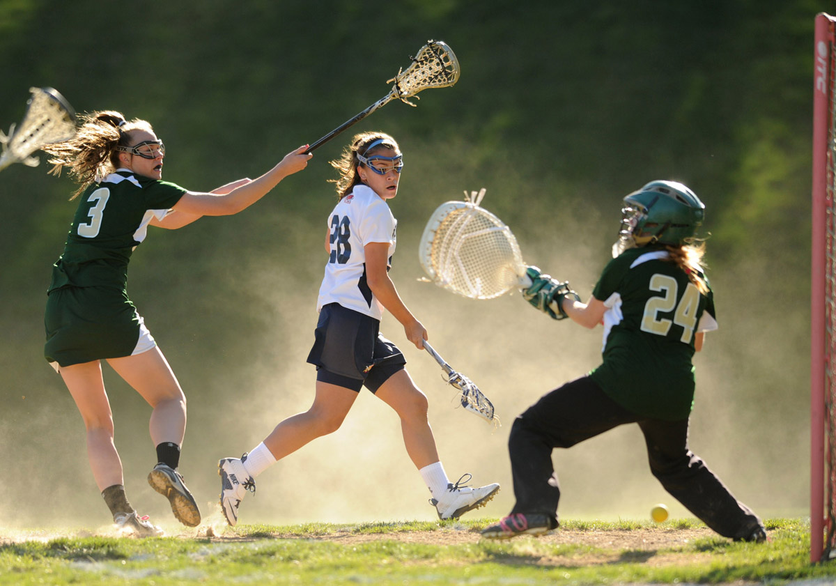 Despite pressure from Century's Alice Mercer, left, Mae Tarr of Notre Dame Prep, center, fires a shot between the legs of Century goalie Allison Remenapp during a girls lacrosse game at Notre Dame Prep in Towson, Md., on Saturday, April 7, 2012. The shot was wide of the goal. (Brian Krista/Patuxent Homestead)