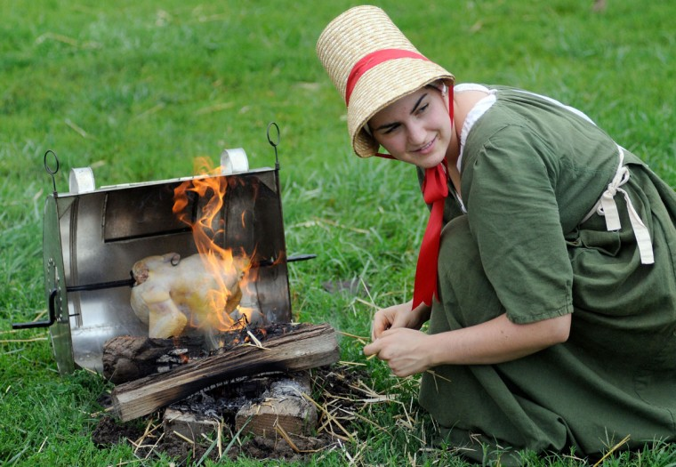September 9, 2011: Volunteer re-enactor Alisa Beverley of Fells Point cooks a chicken the way women did around 1812 while dressed in period clothing at Fort McHenry in Baltimore. (Steve Ruark/Baltimore Sun)