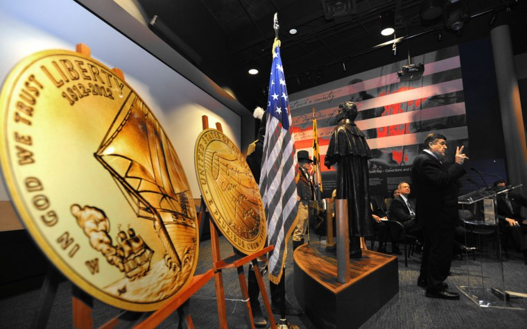 March 5, 2012: At Fort McHenry National Monument and Historic Shrine, a ceremony was held to kick off the sale of two commemorative coins which will help fund the Bicentennial Celebration of the War of 1812 and the Star-Spangled Banner. At the podium is Congressman Dutch Ruppersberger who, along with Sen. Ben Cardin, sponsored legislation to create the coins. Seated behind the Congressman is Governor Martin O'Malley. In the foreground left is a very large model of the gold coin. The U.S. Mint will sell 100,000 gold coins and 500,000 silver coins. (Algerina Perna/Baltimore Sun)