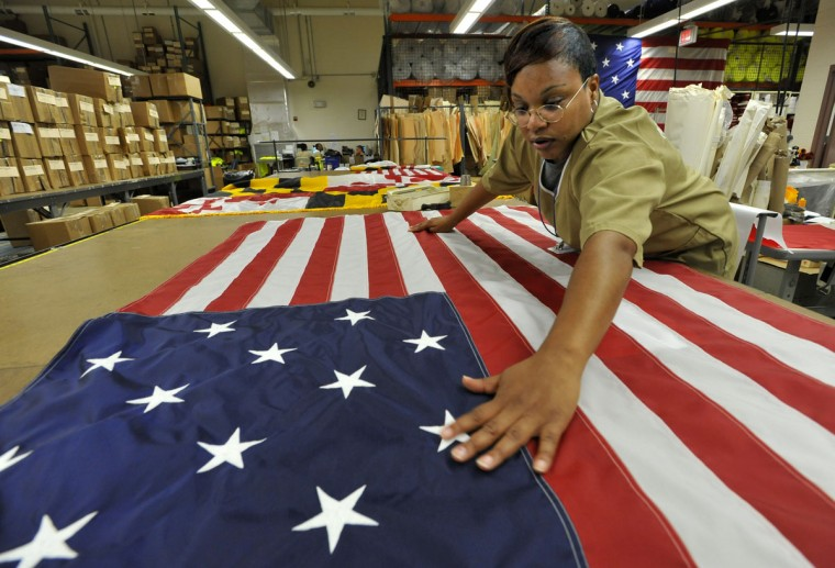 June 14, 2011: Natasha Fowlkes, an inmate at the Maryland Correctional Institution for Women, is a line supervisor in the Maryland Correctional Enterprises sew plant, where they produce U.S., Maryland and War of 1812 flags. Fowlkes is smoothing out a flag to fold after inspecting it. (Amy Davis/Baltimore Sun)