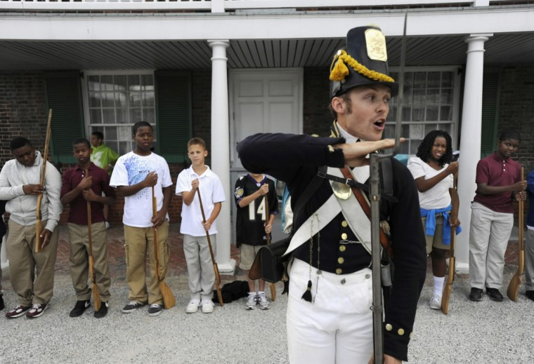 September 10, 2010: Aaron Bradford of Sutherland, VA, leads 7th grade students from Francis Scott Key Elementary/Middle School in the musket drill. Bradford is dressed in the uniform of a 3rd Regiment US Corps of Artillery soldier. The uniform would have been used late in the War of 1812. Nearly 1,400 state school children took part in Young Defenders Day at the Fort McHenry National Monument and Historic Shrine. (Kim Hairston/Baltimore Sun)
