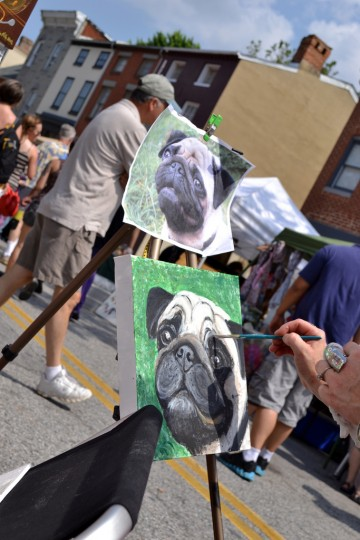 Artist Ania M. Milo paints a dog from the Internet at the SoWeBohemian Arts & Music Festival. (Steve Earley/Baltimore Sun)