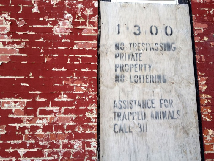 "A vacant rowhouse in West Baltimore with distressed bricks, peeling paint, and a ""No Trespassing"" sign. (Olivia Hubert-Allen/Baltimore Sun)"