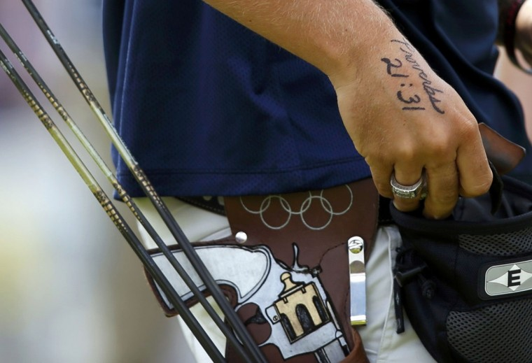 A tattoo of a Bible verse is seen on the hands of Brady Ellison of the U.S. as he prepares to take aim during the men's archery team quaterfinals at the Lords Cricket Ground during the London 2012 Olympics Games July 28, 2012. (Suhaib Salem/Reuters)