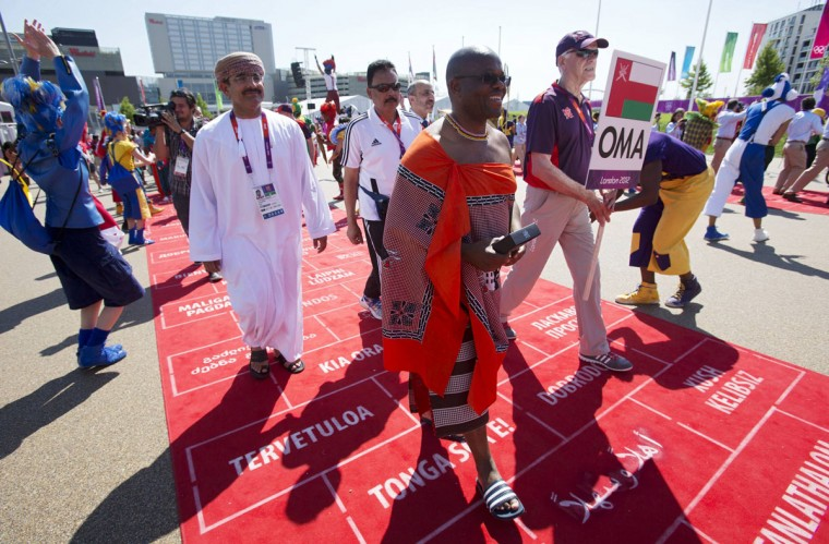 Representatives from Oman and Swaziland walk down a red carpet during a Welcoming Ceremony in the Olympic Village before the London 2012 Olympic Games July 24, 2012. (Neil Hall/Reuters)