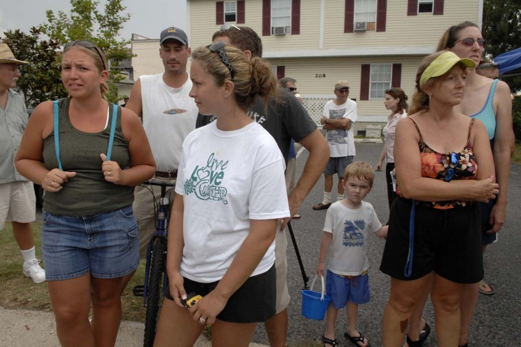 July 30, 2007: Beach vacationers Nikki Amos, left, with friend Elizabeth Davis, second from left in front, watch FBI investigators search the grounds around an Ocean City house where four dead infants were found. (Amy Davis/Baltimore Sun)