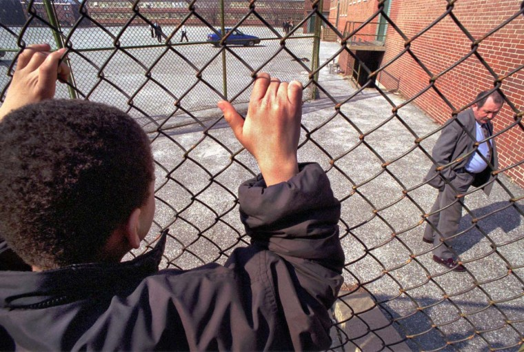 March 15, 1995: Police investigate the scene near South Bethel Street behind Lombard Middle School, where the body of a white, adult female was found at the bottom of a sunken stairwell. Joey Mosby, a 6th grader at the school, watches the detectives. (Amy Davis/Baltimore Sun)