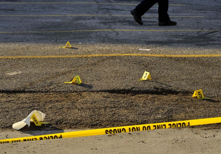January 9, 2011: An officer walks by the evidence markers at a homicide investigation in a parking lot on West Franklin Street near the Select Lounge. A plain-clothes officer was killed by another officer called to the scene after gunfire erupted outside the club. One civilian, among the six people in all who were shot, was also killed in the chaos. (Amy Davis/Baltimore Sun)