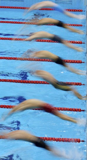 Competitors dive from the starting blocks during their men's 100m backstroke heat during the London 2012 Olympic Games at the Aquatics Centre July 29, 2012. (Toby Melville/Reuters)