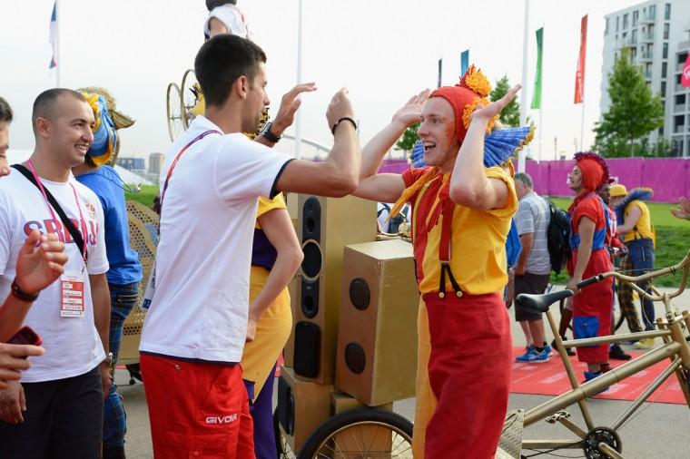 Novak Djokovic of Serbia is greeted by a performer during the official Serbian Team Welcome Ceremony to the Athletes' Village at the Olympic Park on July 25, 2012 in London, England. (Pascal Le Segretain/Getty Images)