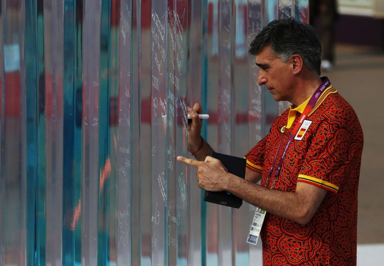 Chef de Mission of Spain Cayetano Cornet Pamies signs the truce wall during a Welcoming Ceremony in the Olympic Village in London, July 25, 2012. (Mark Blinch/Reuters)