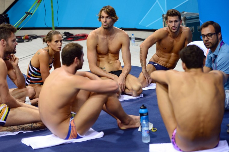 France's Laure Manaudou (2D-L) and Camille Lacourt (C) listen to team mates during a training session ahead of the London Olympic Games on July 24, 2012 at the Aquatics Centre in London. France's 2004 Olympic 400m freestyle swimming champion Laure Manaudou recently said she was not obsessed with winning a medal at the London Games and instead was seeking to just enjoy her third Olympics. (Christophe Simon/AFP/Getty Images)