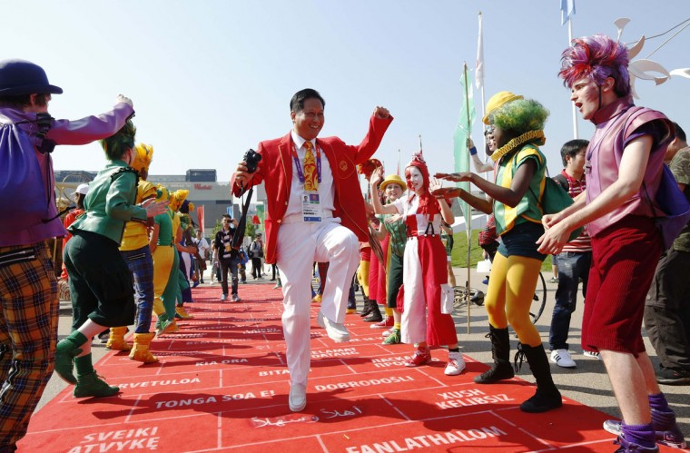 A member of the Chinese Olympic delegation joins performers during a Welcoming Ceremony for the team in the Athletes Village at the Olympic Park in London July 25, 2012. (Luke MacGregor/Reuters)