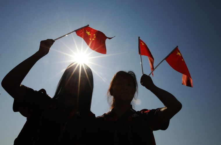 Members of the Chinese delegation wave flags during a Welcoming Ceremony for the Chinese Olympic team in the Athletes Village at the Olympic Park in London July 25, 2012. (Luke MacGregor/Reuters)