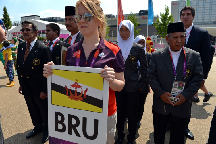Brunei officials and athletes listen to the Olympic anthem during a Flag Raising Ceremony at The Olympic Village in London on July 25, 2012, two days before the start of the London 2012 Olympic Games.2012. (Saeed Khan/AFP/Getty Images)