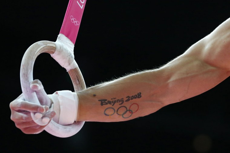 A picture shows the Olympic tattoo of Spain's gymnast Sergio Munoz as he competes on the rings during the men's qualification of the artistic gymnastics event of the London Olympic Games on July 28, 2012 at the 02 North Greenwich Arena in London. (Thomas Coex/AFP/Getty Images)