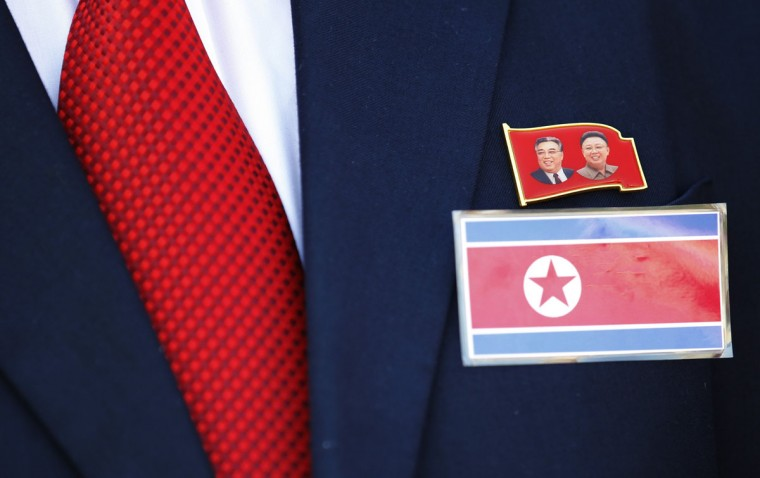 A member of the North Korean delegation wears a badge showing the pictures of former leaders Kim Il-sung (L) and Kim Jong-il during a Welcoming Ceremony in the Athletes Village at the Olympic Park ahead of the London 2012 Olympic Games July 25, 2012. (Luke MacGregor/Reuters)