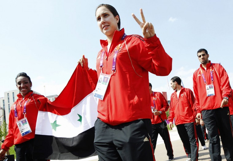 An athlete gestures as she arrives carrying the Syrian flag at a Welcoming Ceremony in the Athletes Village at the Olympic Park ahead of the London 2012 Olympic Games July 25, 2012. (Luke MacGregor/Reuters)