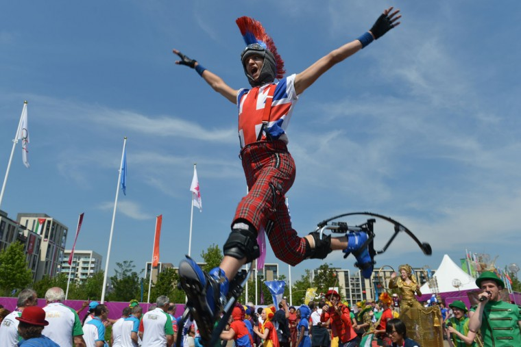 An artist performs on jumping stilts during a Welcoming Ceremony for athletes at the Olympic Village in London on July 25, 2012, two days before the start of the London 2012 Olympic Games. (Adek Berry/AFP/Getty Images)