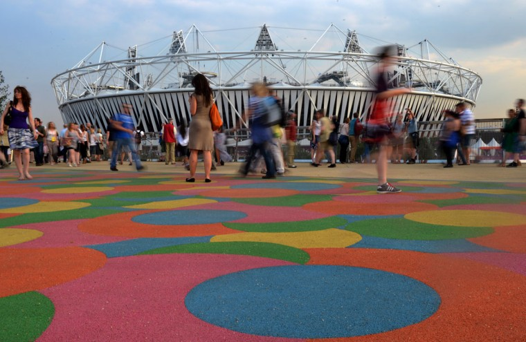 Visitors walk past the Olympic Stadium in the Olympic Park before the last rehearsal of the Opening ceremony in east London on July 25, 2012, two days before the start of the London 2012 Olympic Games. (Johannes Eisele/AFP/Getty Images)