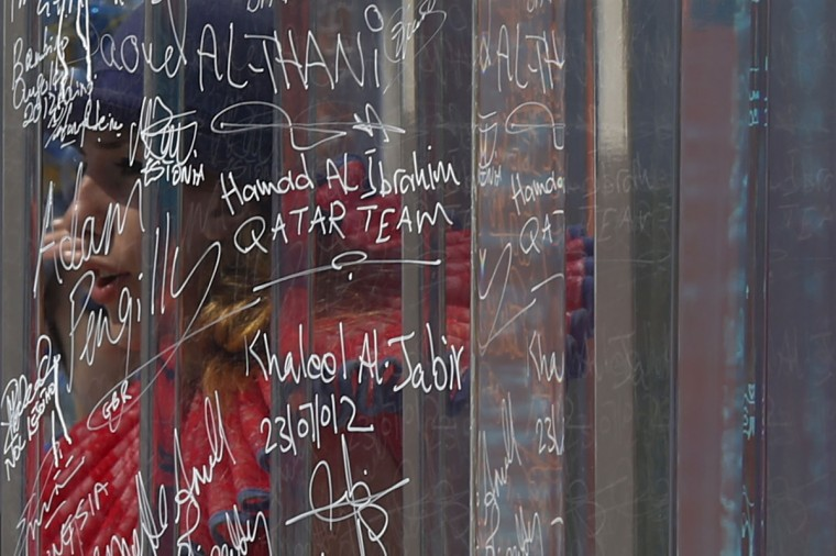 A performer is seen through the transparent Truce Wall which was signed by the Chef-de-Missions of countries taking part in the London 2012 Olympic Games at the Athletes Village in the Olympic Park on July 26, 2012. (Adrees Latif/Reuters)
