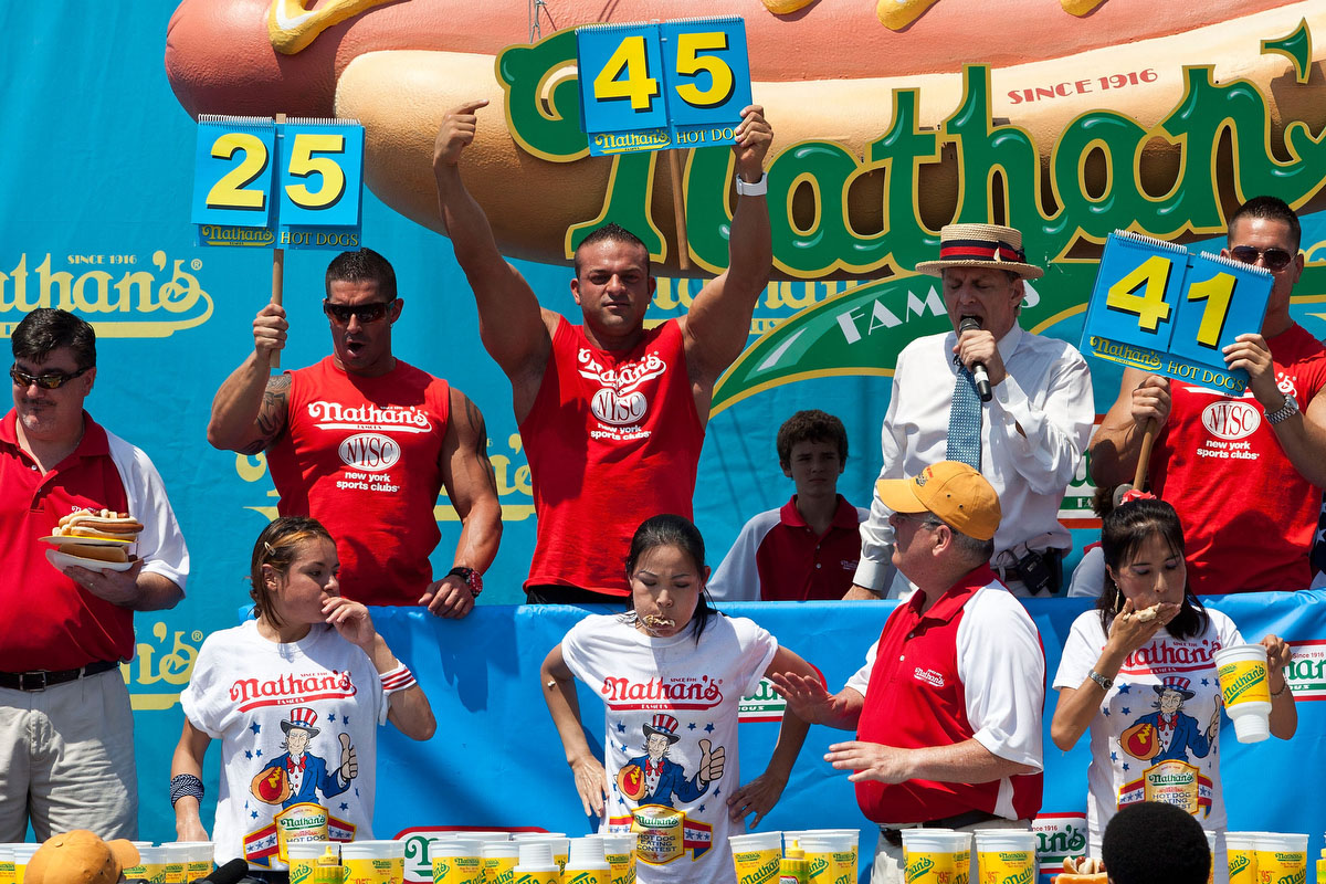 Competitive eater Sonya Thomas, center on the bottom row, rests moments after the women's division of the Nathan's Famous International Hot Dog Eating Contest finishes at Coney Island in the Brooklyn borough of New York City. (Andrew Burton/Getty Images)