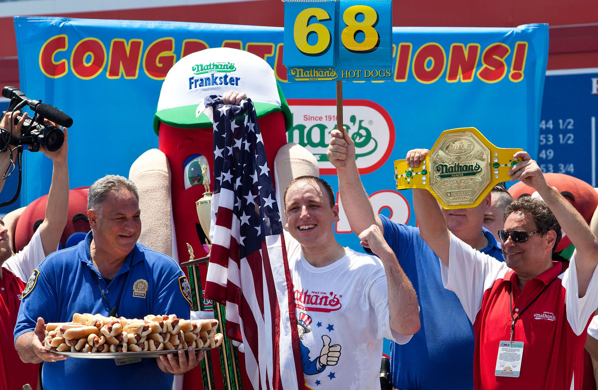 Competitive eater Joey Chestnut celebrates his victory after winning the Nathan's Famous International Hot Dog Eating Contest at Coney Island. Chestnut won the men's division by successfully tying his own world record by eating 68 hot dogs in 10 minutes; he has now won the competition six years in a row. (Andrew Burton/Getty Images)