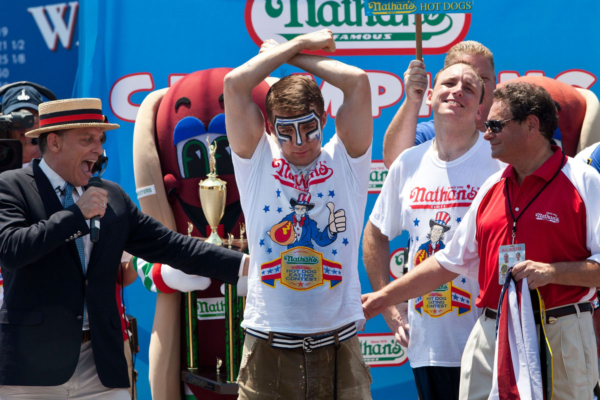 Competitive eater Tim Janus celebrates his second place win in the men's division of the Nathan's Famous International Hot Dog Eating Contest at Coney Island. Janus earned second place, with 52 hot dogs in 10 minutes. (Andrew Burton/Getty Images)