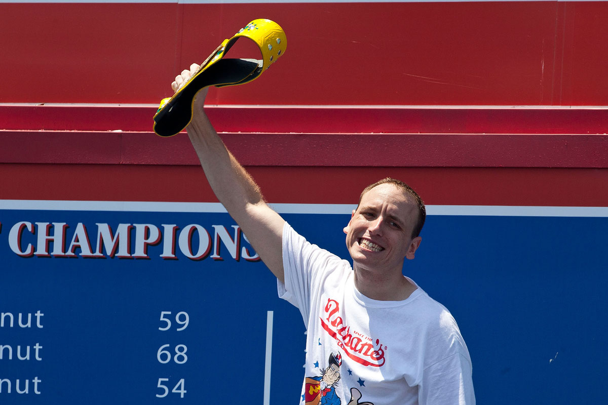NEW YORK, NY - JULY 04: Competitive eater Joey Chestnut waves to the crowd before competing in the Nathan's Famous International Hot Dog Eating Contest at Coney Island on July 4, 2012 in the Brooklyn borough of New York City. Chestnut won the men's division by successfully tying his own world record by eating 68 hot dogs in 10 minutes; he has now won the competition six years in a row. (Photo by Andrew Burton/Getty Images) ORG XMIT: 147861003
