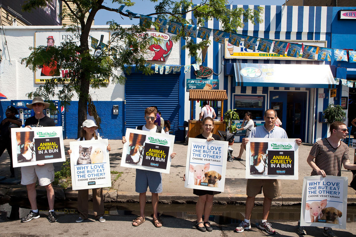Animal rights protestors stand outside Nathan's Famous Hot Dogs prior to the Nathan's Famous International Hot Dog Eating Contest at Coney Island in the Brooklyn, New York City. (Andrew Burton/Getty Images)