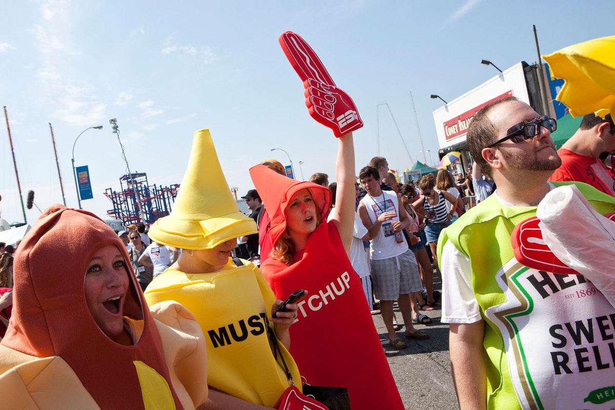 People dressed as various condiments cheer prior to the Nathan's Famous International Hot Dog Eating Contest at Coney Island. Joey Chestnut won the men's division by successfully tying his own world record by eating 68 hot dogs in 10 minutes; he has now won the competition six years in a row. (Andrew Burton/Getty Images