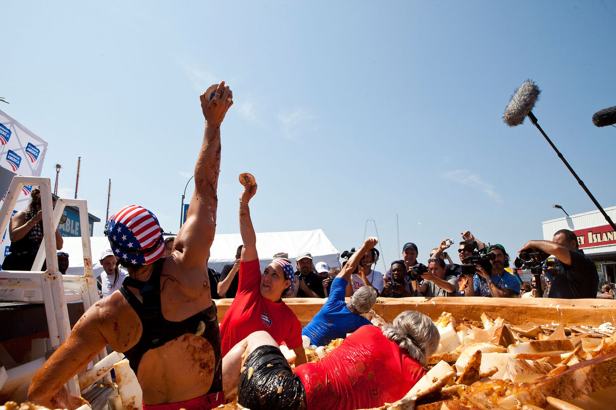 "People compete in an ""Apple Pie Dive"" contest prior to the Nathan's Famous International Hot Dog Eating Contest at Coney Island in the Brooklyn borough of New York City. (Andrew Burton/Getty Images)"