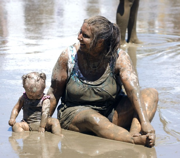 "People play in a giant lake of mud at the 25th annual ""Mud Day."" The event, which features a 75' by 150' pit filled with 20,000 gallons of water and 200 tons of topsoil, draws about a thousand children each year. (Bill Pugliano/Getty Images)"